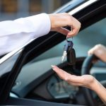 Man hands keys over for car rental insurance